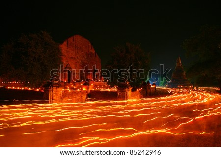 Walk with lighted candles in hand around a temple