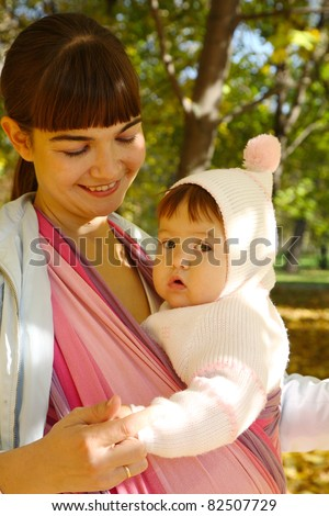 Walk with the child in a baby sling. - stock photo