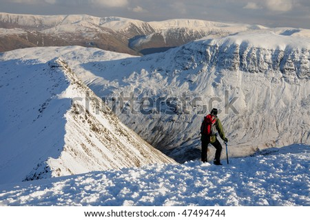 Walker enjoying the view over Striding Edge in winter, English Lake District