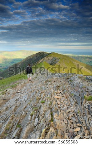Walker on Whiteside above Gasgale Crags, mountain ridge in the English Lake District
