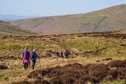 Walkers heading towards Bullpot. Ease Gill Kirk is one of the most atmospheric places in the Yorkshire Dales. It is a steep sided limestone gorge found towards the lower end of Ease Gill