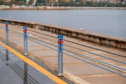 Walking and cycling path with steel rope safety barrier in the background sea