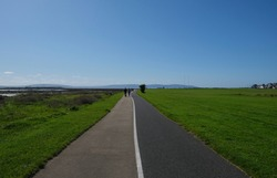 Walking & bicycle path from Galway to Salthill, Ireland with views of the grassy sports field and hills across the bay, with silhouetted figures walking