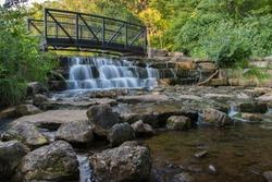 walking bridge over small waterfall at public park in Springfield Missouri.