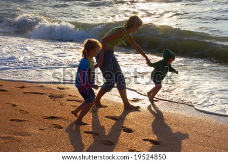 Walking family on evening sandy beach and surf