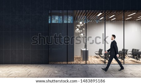 Walking in the evening on a street businessman past business center with minimalistic style auditorium with lights, black chairs and wooden floor.