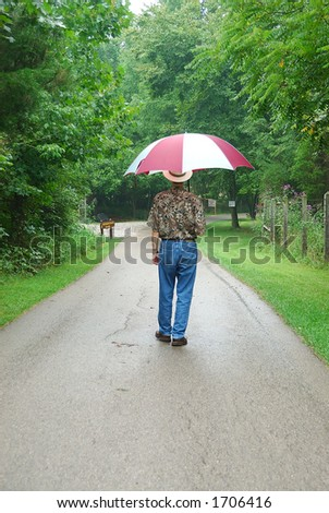 Walking in the forest on a rainy day with a large umbrella.