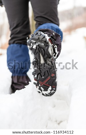 Walking legs and shoes on snow trail in winter forest. Recreation and healthy lifestyle outdoors in nature. Trekking shoes tracks