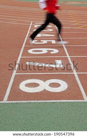 Walking man legs on runway in a sports ground in a middle school