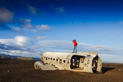 Walking man on the old crashed plane abandoned on Solheimasandur beach near Vik in Iceland