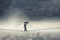 Walking on rope businessman with black umbrella