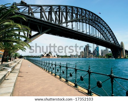 Walking on the path that leads beneath the Sydney Harbour Bridge in Australia.  Cityscape of Sydney behind.