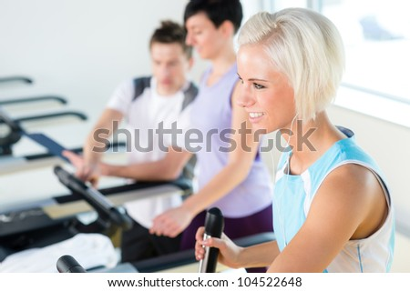 Walking on treadmill young people cardio workout at fitness center - stock photo