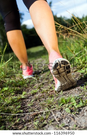 Walking or running legs in forest, adventure and exercising in summer nature. Jogging or training outside in summer nature, motivational health and fitness concept.