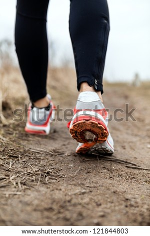 Walking or running legs sport shoes, fitness and exercising in autumn or winter nature. Cross country or trail runner outdoors