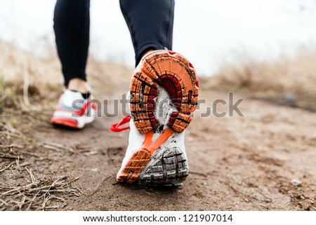 Walking or running legs sport shoes, fitness and exercising in autumn or winter nature. Cross country or trail runner outdoors.