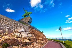 Walking path around the stone monument to Salawat Yulaev in a summer sunny day with blue sky, bottom view in front of the rocks. Salavat Yulayev, Ufa, Bashkortostan, Russia.