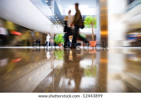 Walking people in modern business center. Special zoom blur effect.