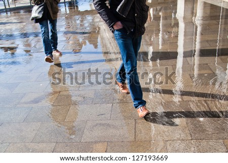walking people on the flooded St. Mark's square in Venice