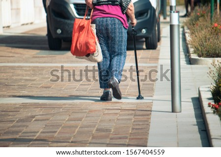 walking stick detail, an old female person with bags walks using a support for deambulation