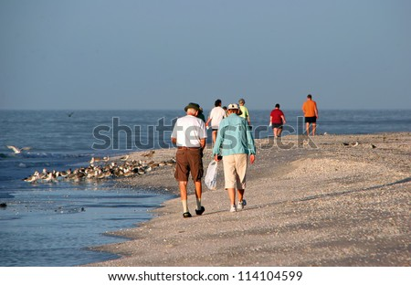 Walking the Beach Searching for Seashells Sanibel Florida - stock photo