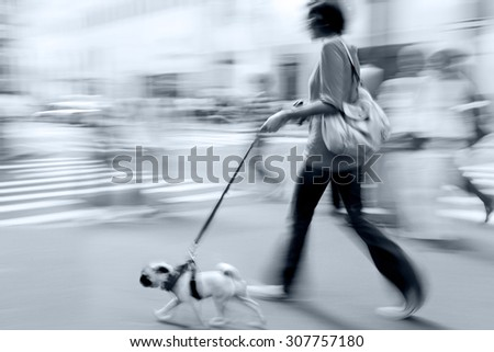 walking the dog on the street in motion blur and blue tonality