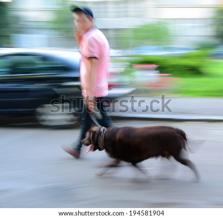 Walking the dog on the street. Intentional motion blur