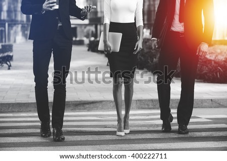 Walking to success together. Cropped image of three business people crossing the street #400222711