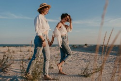 walking two young women having fun on the sunset beach, queer non-binary gender identity, gay lesbian love romance, boho summer vacation style wearing jeans