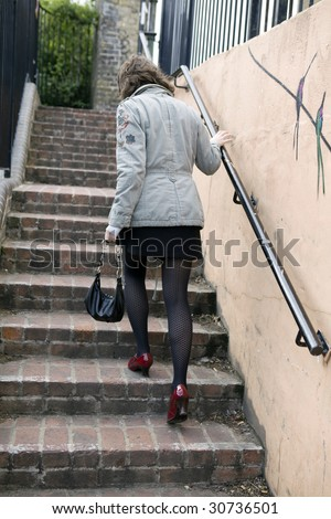 walking up stairs to higher level. Red shoes