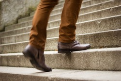 Walking upstairs: close-up view of man's leather shoes  (motion blurred image)