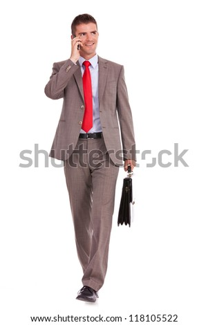 walking young business man with briefcase , looking away from the camera while speaking on his hone, isolated on white background
