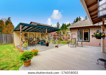Walkout deck with patio area and wood pergola. Pergola furnished with patio dining table set and sofa. Decorated with flower pots