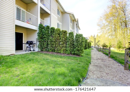 Walkout deck with patio area, green grass, trimmed hedges and wooden fence.