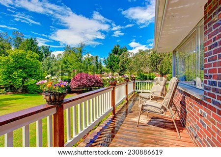 Walkout deck with sitting area decorated with flower pots. Deck overlooking front yard garden #230886619