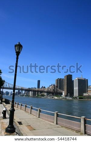 Walkway along Manhattan's Roosevelt Island.  Queensboro Bridge in the background.