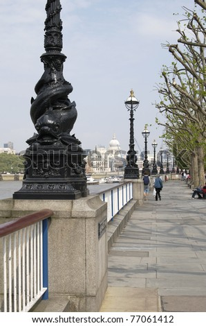 Walkway along River Thames on South Bank at Westminster. London. England. Saint Paul's Cathedral in background.