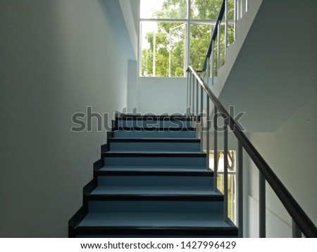 Walkway.Blue stairs.Narrow stairs.Walls and stairs.Stairs inside the building #1427996429