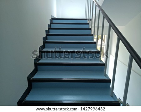 Walkway.Blue stairs.Narrow stairs.Walls and stairs.Stairs inside the building #1427996432