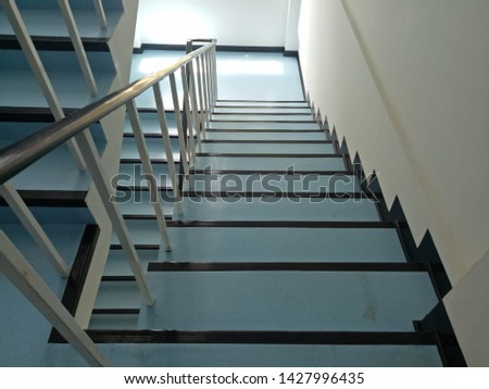 Walkway.Blue stairs.Narrow stairs.Walls and stairs.Stairs inside the building #1427996435