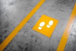 Walkway lane in parking building. Painted yellow footsteps between parallel yellow lines on abstract cement floor. Step by step concept.