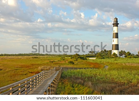 Walkway leading to the Bodie Island lighthouse over marshes of the Cape Hatteras National Seashore against white clouds and a blue morning sky