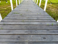 Walkway made of old gray wooden planks with white handrails and white light bulbs. Dock of wooden planks. Old elevated wooden boardwalk in the park. Wooden walkway in the green garden.