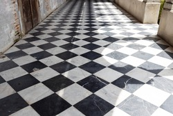 walkway path with checkered pattern marble tiles floor and shadow from outside sunlight in old cement gothic church