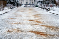 Walkway sprinkled with salt mixtures and sand. De-icing chemicals on pavement. Prevent slipping on road with sand and reagents - technical salt. Icy road and  danger of injury on slippery road