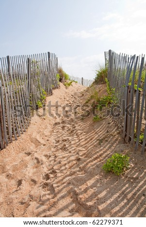 Walkway to a beach in Kitty Hawk on the Outer Banks of North Carolina with wooden fencing to both sides and a bright sky vertical