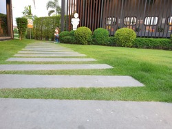 Walkway to the toilet is a large stone slab interspersed with green grass and has signs. Thai in pictures means no smoking