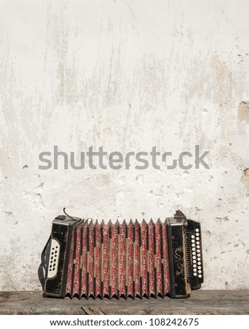 wall and accordion on the bench background - stock photo