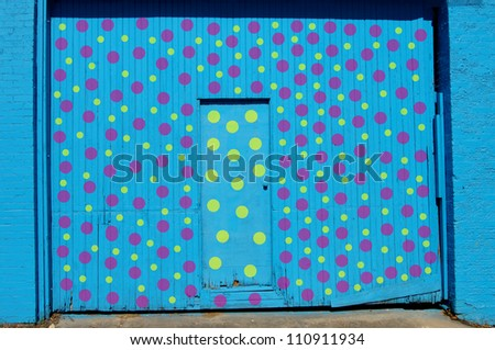 Wall and double door has been painted brilliant blue.  Yellow and purple polka dots decorate surface.