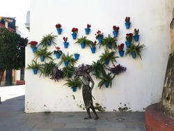 wall art of an iron sculpture woman with flowers and leaves on a white wall.